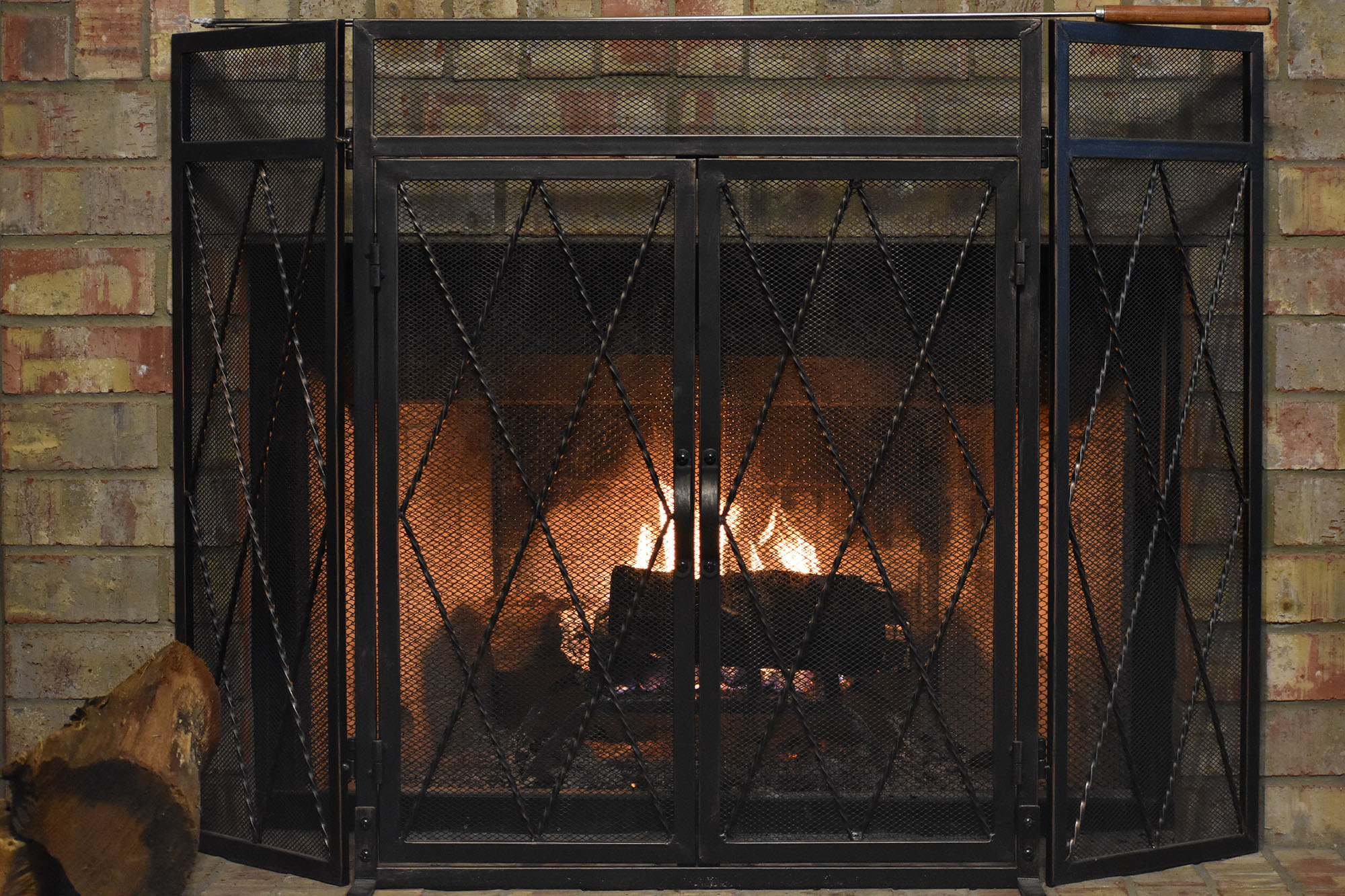 gas fireplace with log and iron screen and blazing fire within