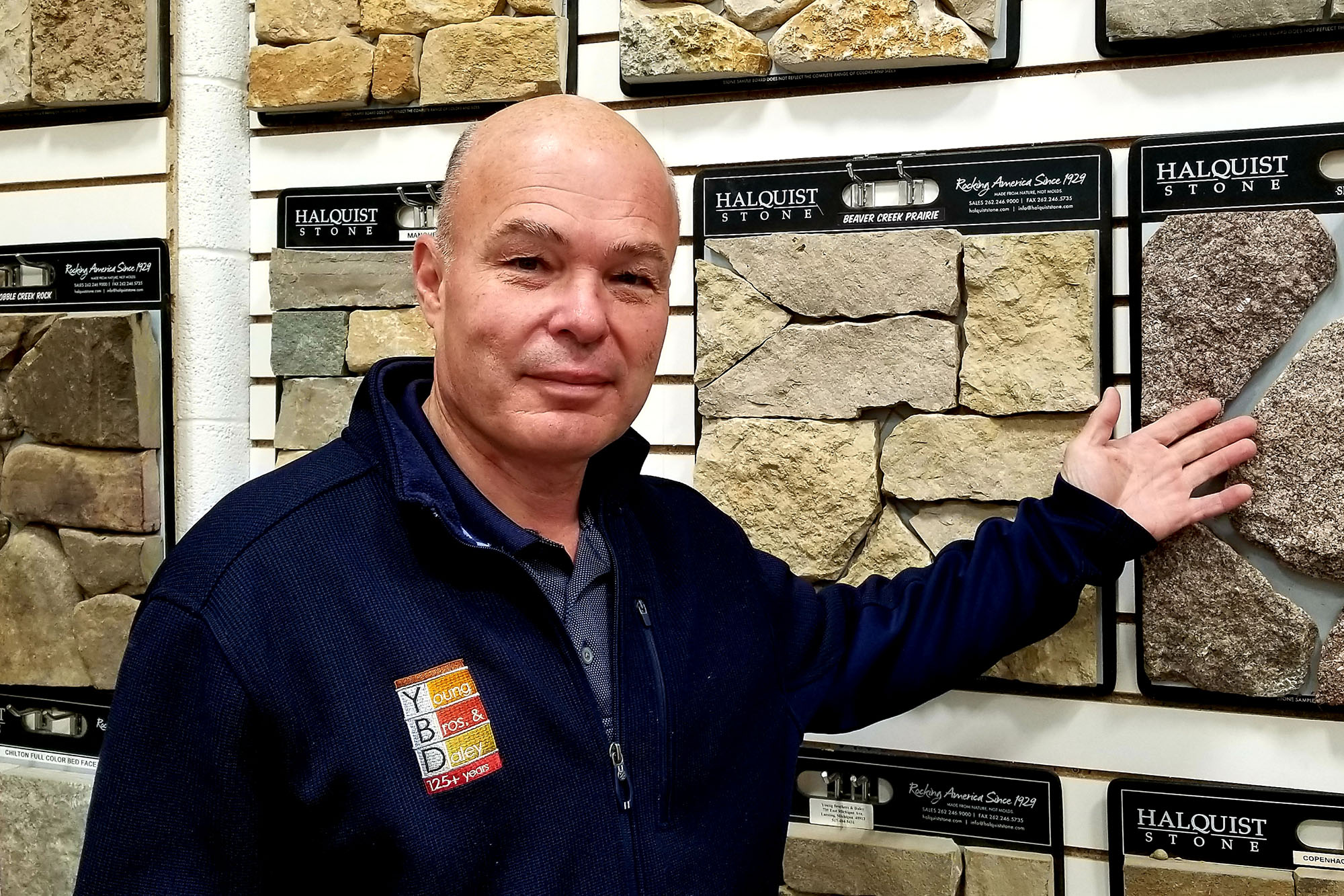 landscape supply store employee with YBD shirt showing stone display